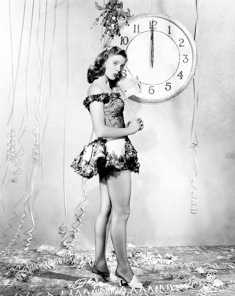 Young woman standing in front of a clock, celebrating New Years Eve.