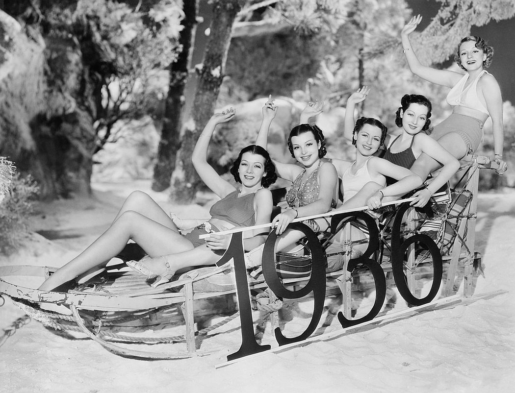 A group of women enjoy a New Year's sledding party.