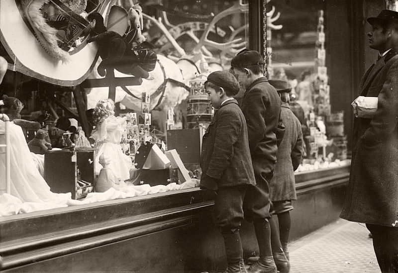 Children looking at Xmas toys in shop window, 1900.