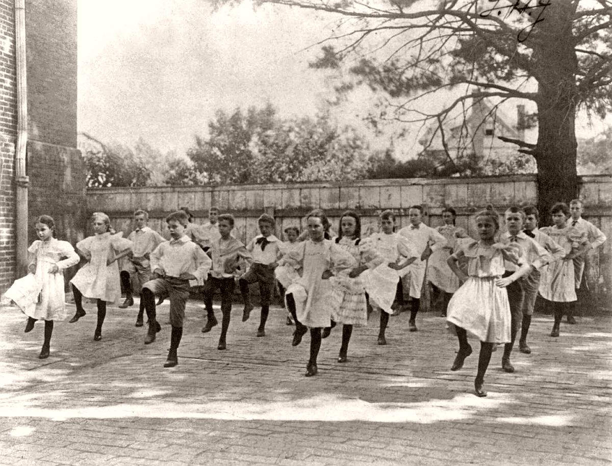 School children learning a dance in a school yard, Washington, DC, 1899