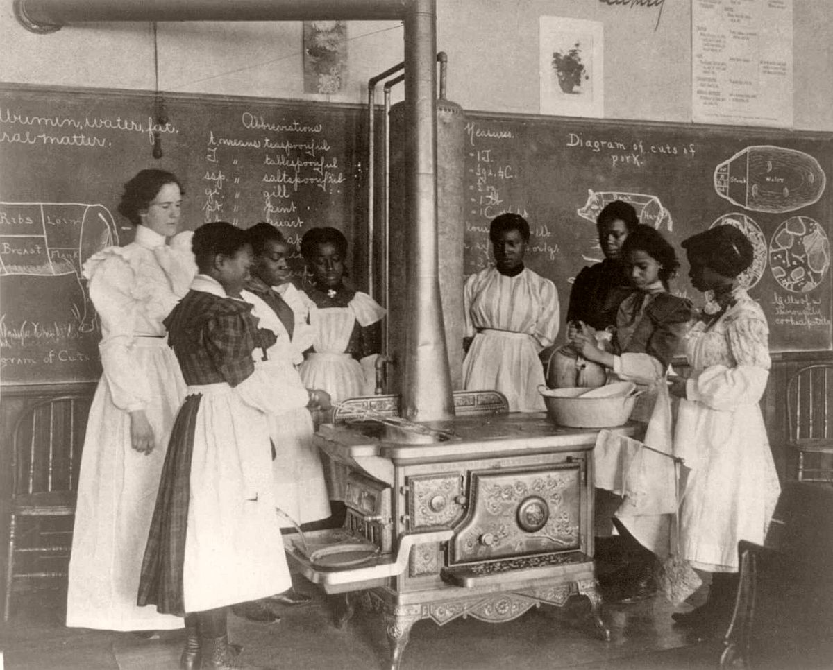 African American schoolgirls with teacher, learning to cook on a wood stove in classroom, 1899