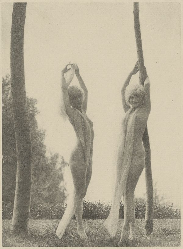 Two Partially Nude Females in Blond Wigs Stretching Outdoors