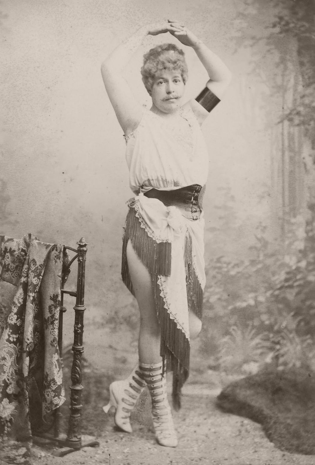 Man standing with arms joined above head, wearing a corset type belt, tasselled skirt and ladies calf length stud-fastening boots. He has his hands raised above his head on a ballet style pose.