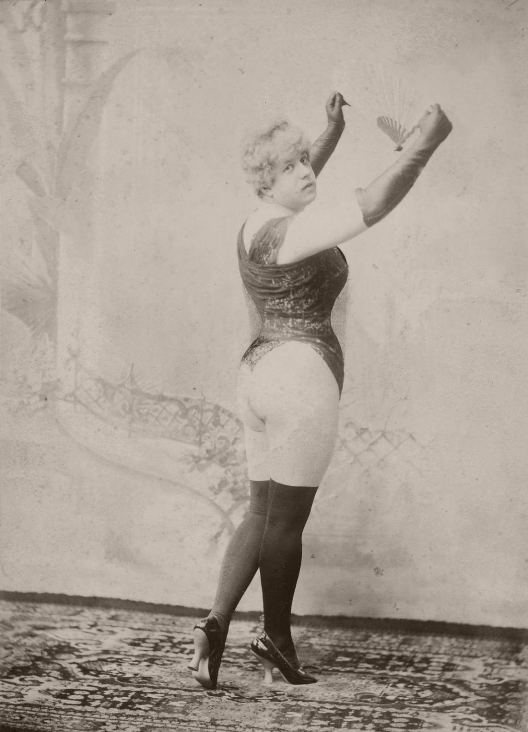 Man standing facing background and turning head towards front, wearing corset or bodice, ladies shoes and thigh high stockings, long gloves and holding an open fan above his head with both arms.