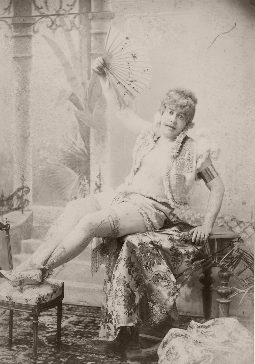 Man seated, wearing ladies shoes and stockings, ruffle or lace edged open top (bare chested) and shorts or skirt, holding up an open fan. He is seated on a table with his feet resting on a stool.