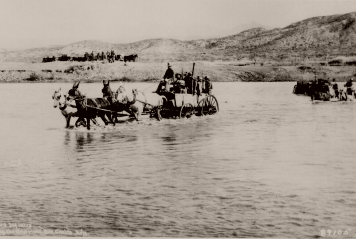 Co. B~ 10th Infantry~, crossing Gila River in buckboard wagons near San Carlos, Ariz. Terr., ca. 1885.