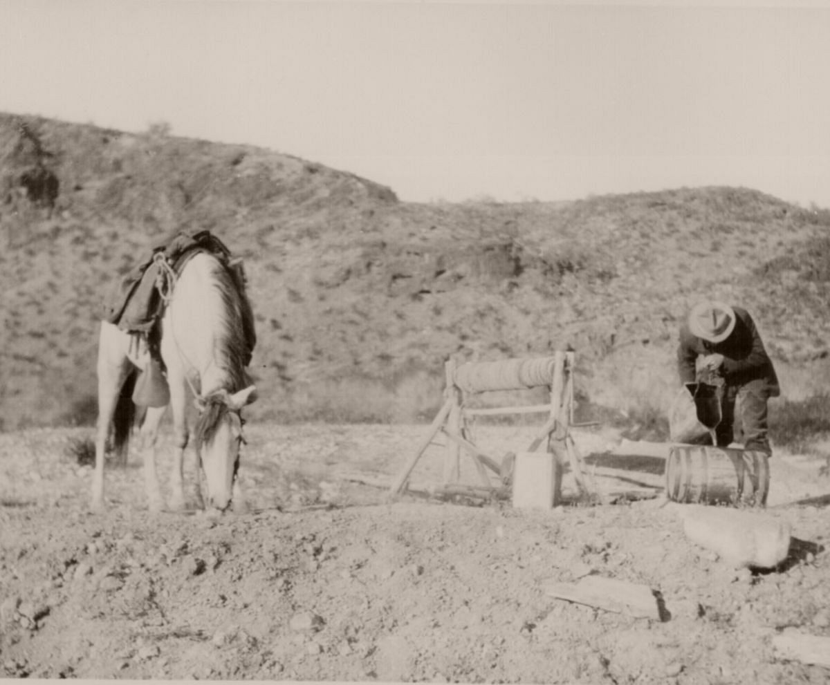 A rider fills his keg from a desert well 30 miles north of Palomas, Ariz. Terr. His horse refreshes himself nearby. April 5, 1907.
