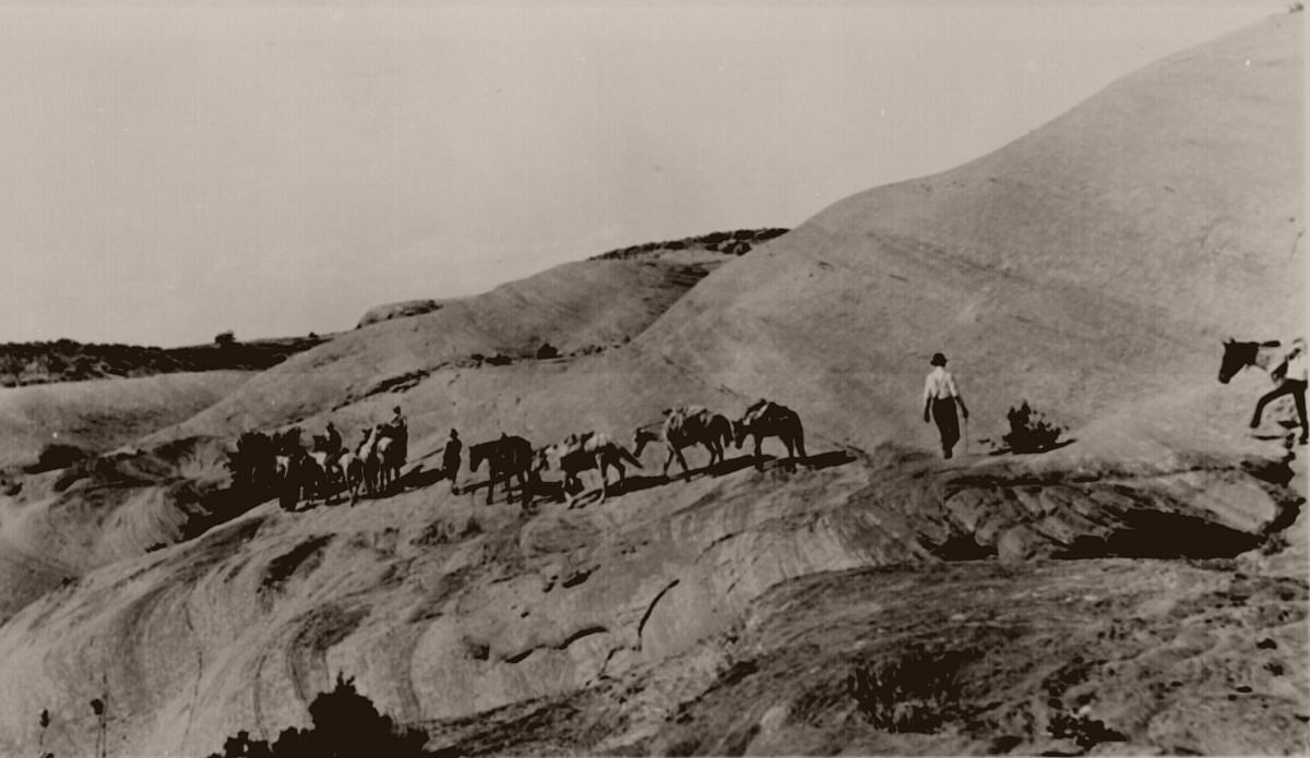 Discovery party and horses on hot, slick rocks west of Navajo Mountain on their way to Rainbow Bridge, Utah. August 13, 1909.