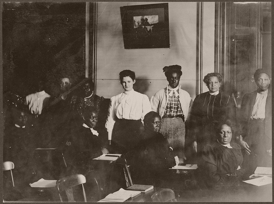 A group of 10 women in a classroom