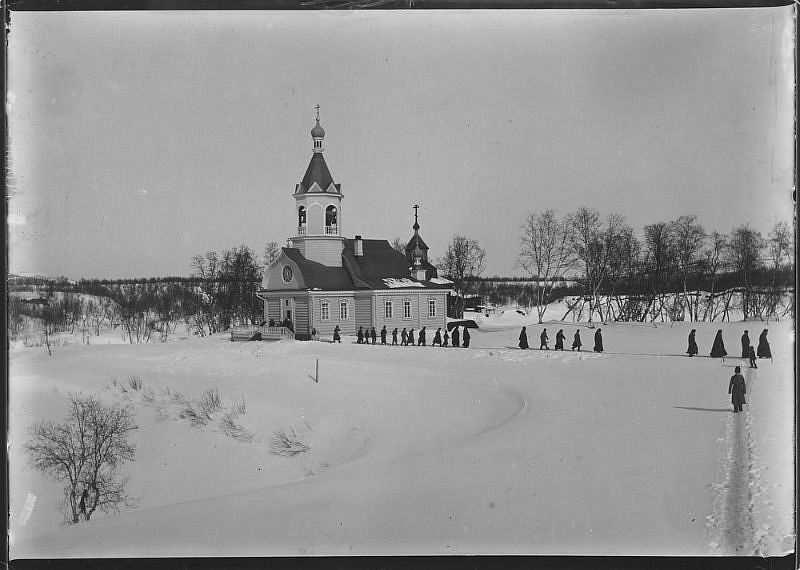 Pechenga monastery church in winter landscape, priests on their way home