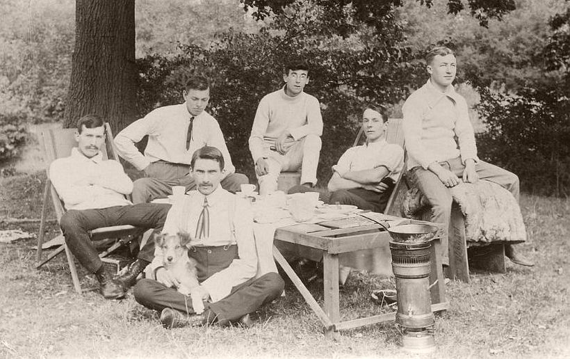 Young men, and a dog, having a picnic