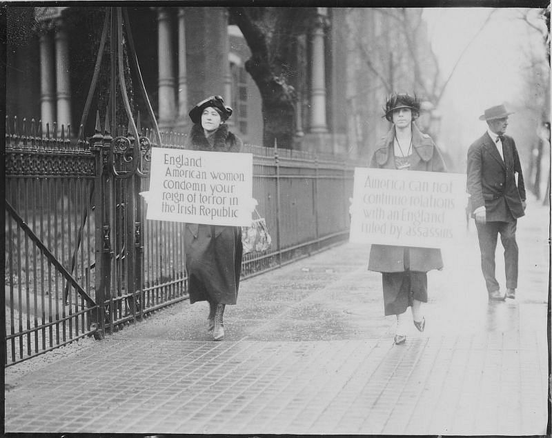 Group of women activists holding protest posters and an American flag, being directed by policemen, at an unidentified location, December 1920
