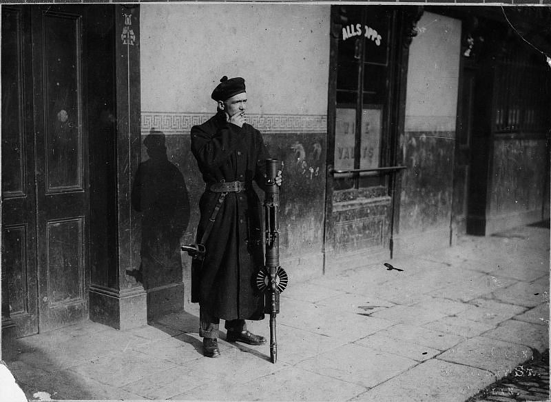 Black and Tans man in uniform on duty, smoking and posing with a Lewis gun, Dublin, circa 1920