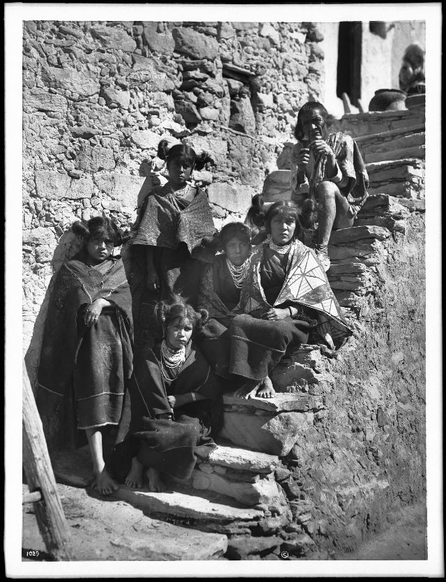 Five young Hopi Indian girls with an old Hopi Indian man sitting on stone steps in the village of Shonguapavi