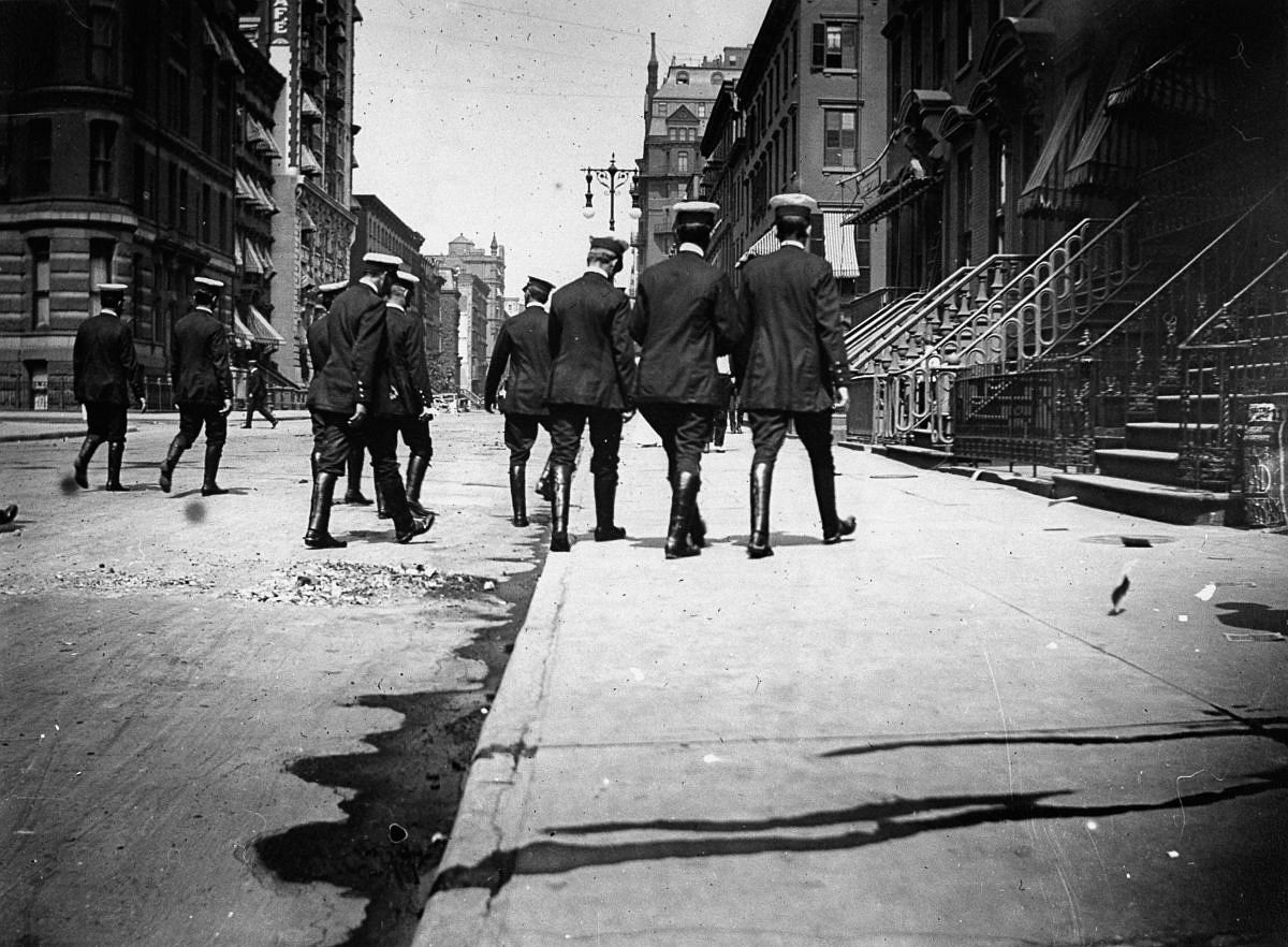1886 - Uniformed officers in riding boots walk down a street.