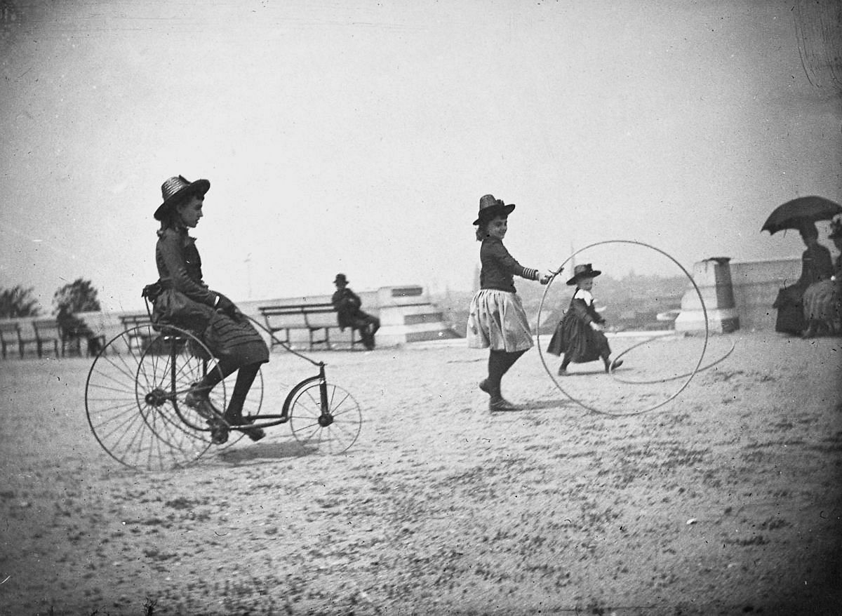 May 22, 1886 - Isabel Harter rides a tricycle while her sister Nellie rolls a hoop in Fort Greene.
