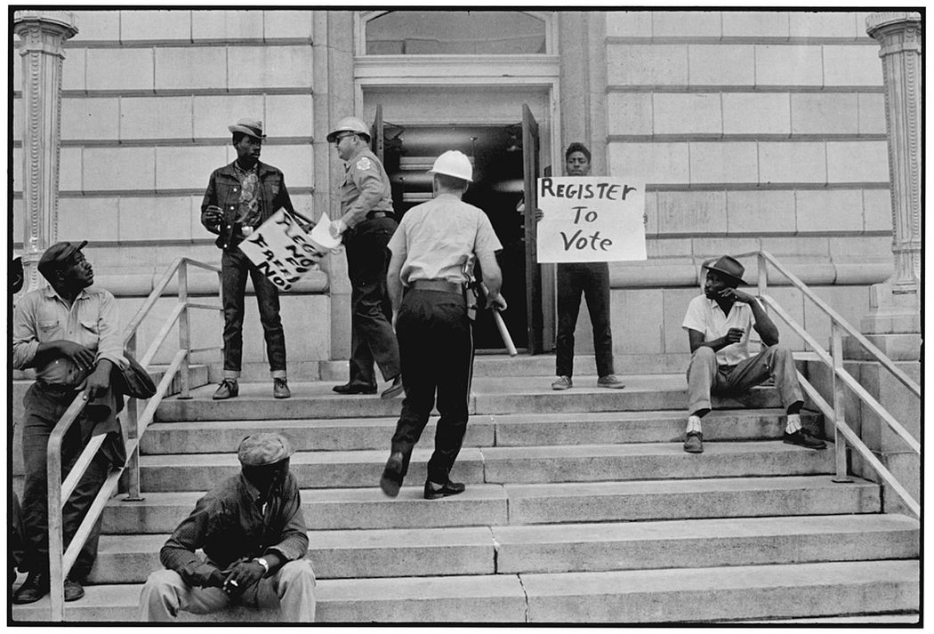 Sheriff Jim Clark arrests two demonstrators who displayed placards on the steps of the federal building in Selma, 1963. Danny Lyon (born 1942). Gelatin silver print, 11 x 14 inches. © Danny Lyon, New York & Magnum Photos, New York / Courtesy Edwynn Houk Gallery, New York.