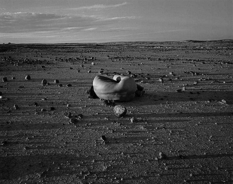 "Judy Dater, ""Self-portrait with Stone, Badlands, South Dakota"", 1981. Gelatin silver print, 14 3/8 x 18 1/4 in. on 16 x 20 in. sheet. Collection of the artist. © Judy Dater"