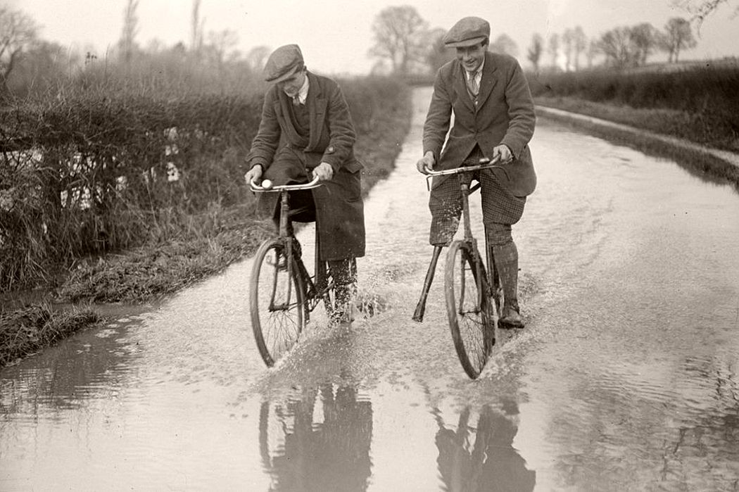 A man with a wooden leg cycles down a flooded road in Berkshire, December 1915.