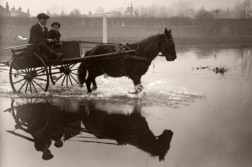 A man and a boy make a journey by pony and trap on the Staines to Windsor Road after flooding in the Thames Valley, December 1915.