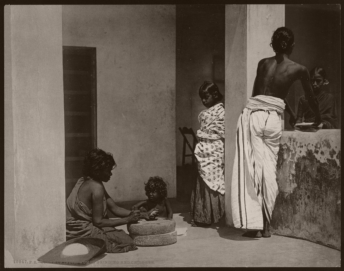 South of India. Women Grinding and Children