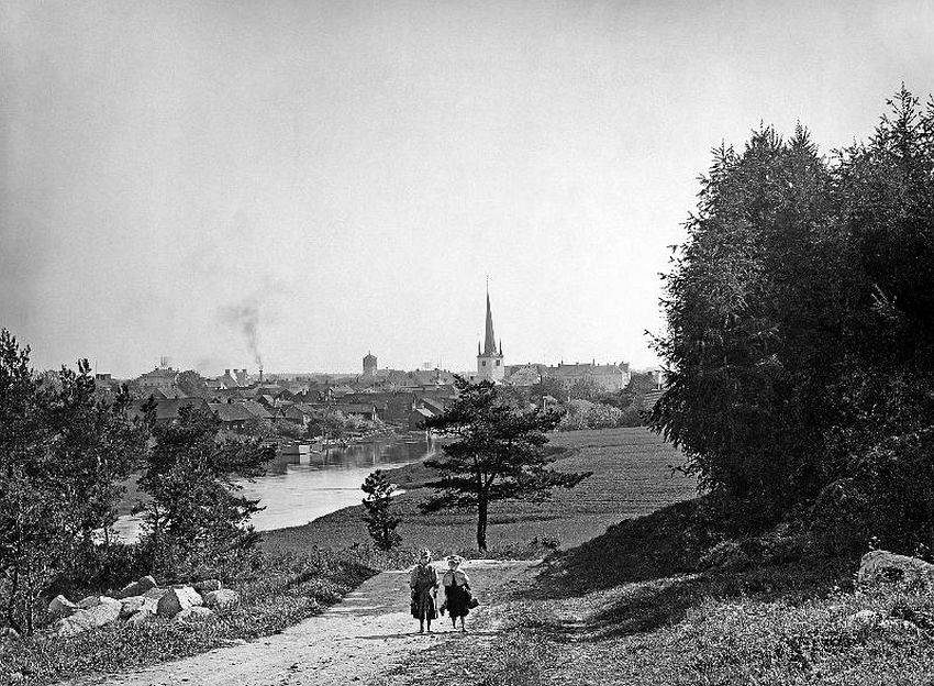 Arboga. Two children on a road by the Arboga Stream. In the middle, the tower of the Holy Trintiy church, and left of it the tower of St. Nicolai church