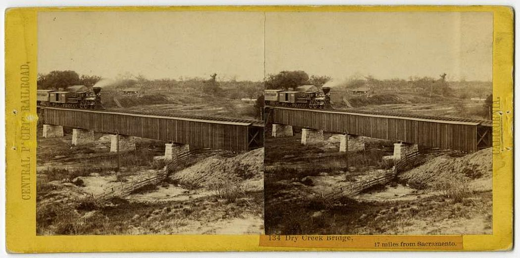 "A stereo card, plate number 134, taken by Alfred A. Hart in California circa 1864. Seventeen miles from Sacramento, a locomotive travels over Dry Creek Bridge, south of Roseville, California. Part of the ""Scenes in the Sierra Nevada Mountains"" stereo card album collection."