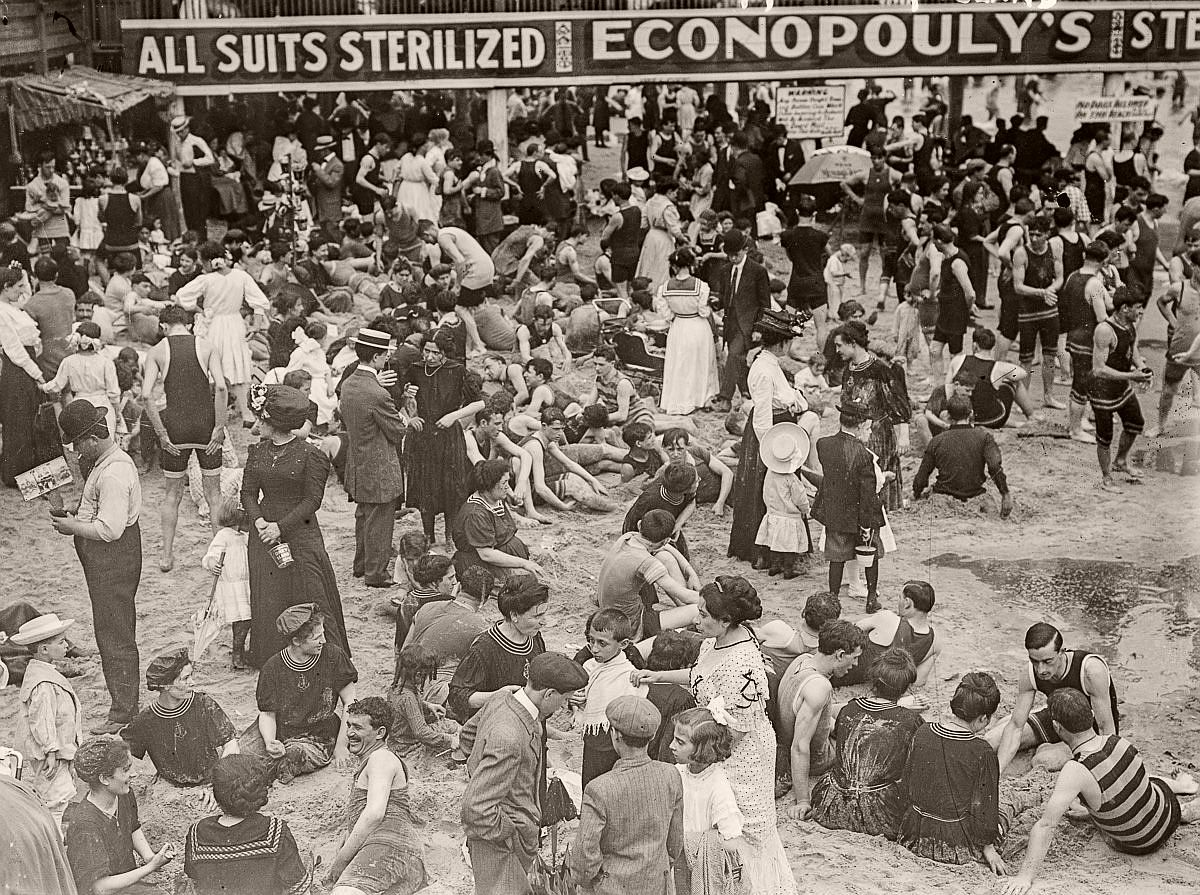 A bathing costume rental company advertises its sterilized suits on the Coney Island beach, c.1900.