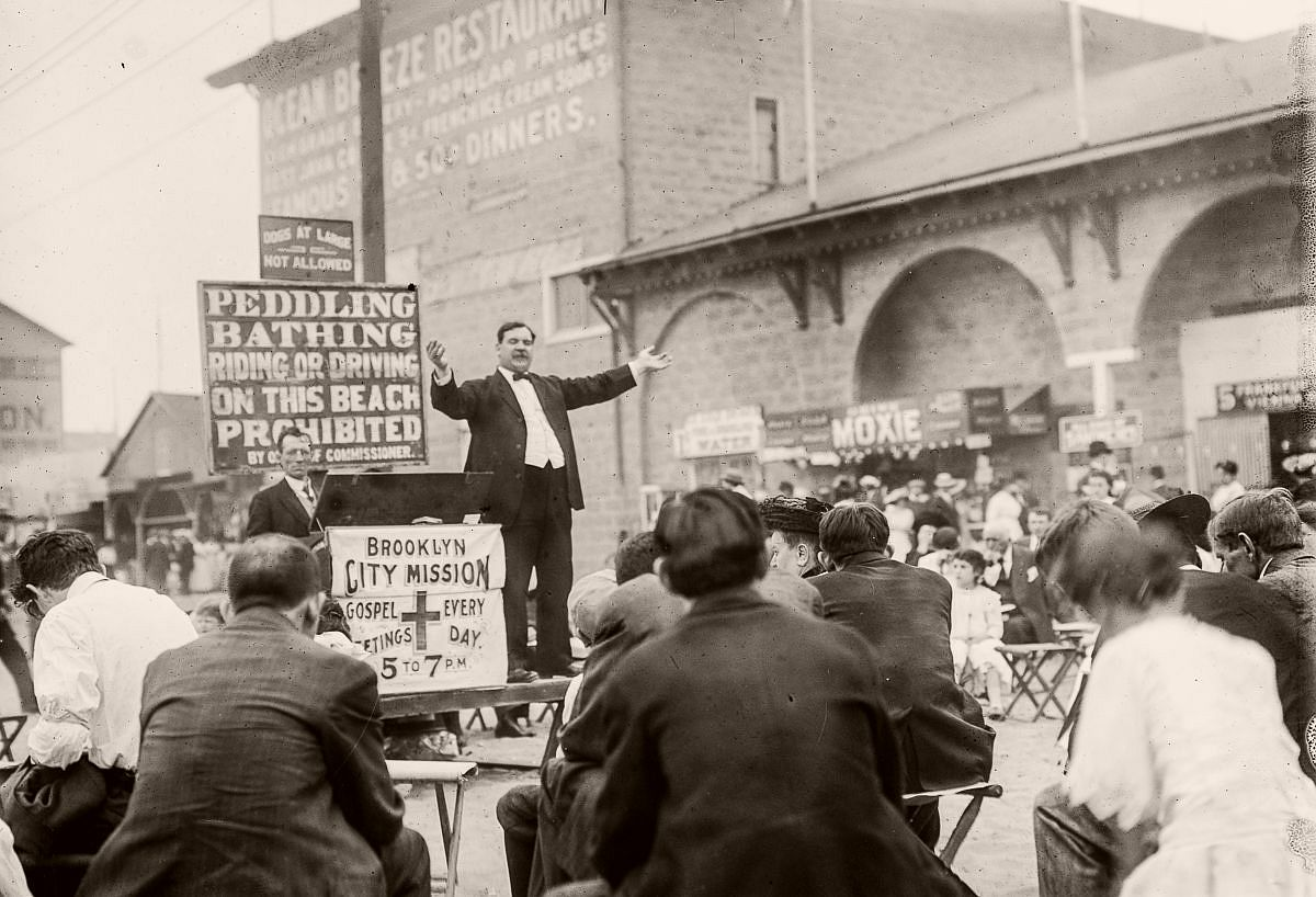 A street preacher proselytizes to revelers on the boardwalk, c.1900.