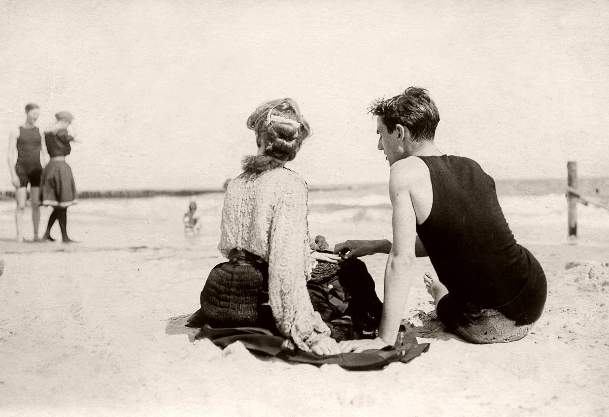 A young couple relax on the beach, 1904.