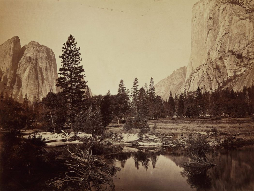 Carleton E. Watkins (American, 1829–1916), View Down the Valley, Yosemite, 1865–1866, albumen silver print. High Museum of Art, Atlanta, gift of Life Insurance Company of Georgia, 1980.119      Carleton Watkins was one of the most highly acclaimed photographers to survey the American West in the 1860s. This sweeping view of the Yosemite Valley conveys the awe-inspiring grandeur of the Western landscape that drew so many travelers and entrepreneurs.     Watkins anchored the composition by flanking the tree-lined valley floor with the iconic landmarks of Cathedral Rocks and El Capitan rising on either side. In the foreground, the glassy Merced River conveys the stillness of a seemingly untouched wilderness.