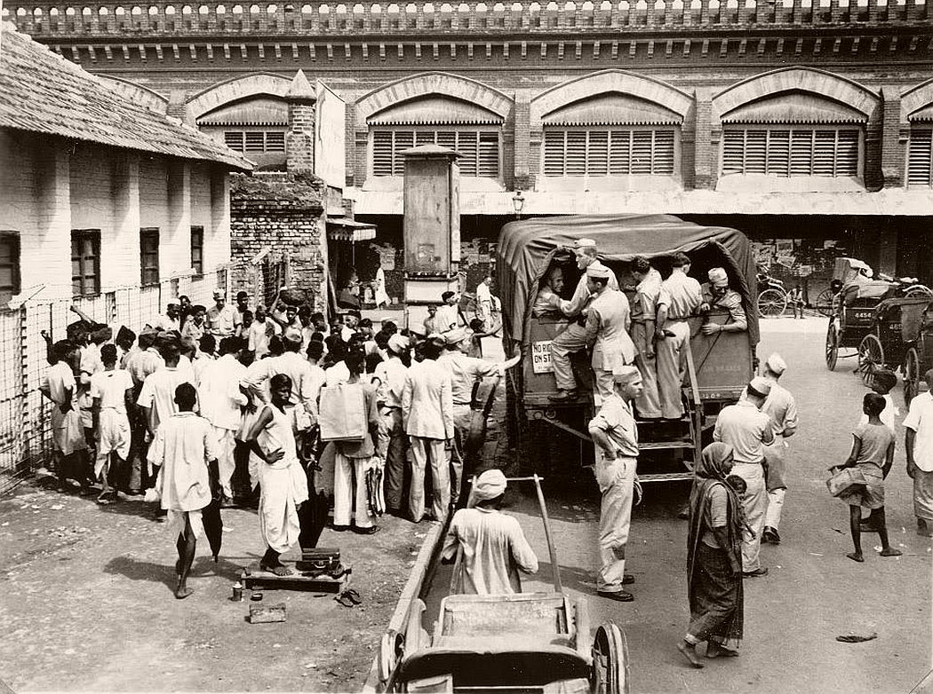 Crowd gathers round a sidewalk performer at bus stop while GI's take temporary advantage of an overhead view from steps of a camp bus. This is a good spost for hawkers, beggars, shoe shine boys, showmen to work on the bankroll of the 'rich American soldier'.