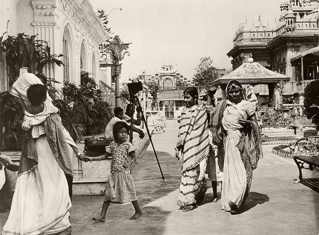 Indian women, dressed in the native Saree, return from prayer at Jain Temple. Little girls wear European dress usually until the marriage age, although some mothers like to dress the little girls in Sarees.