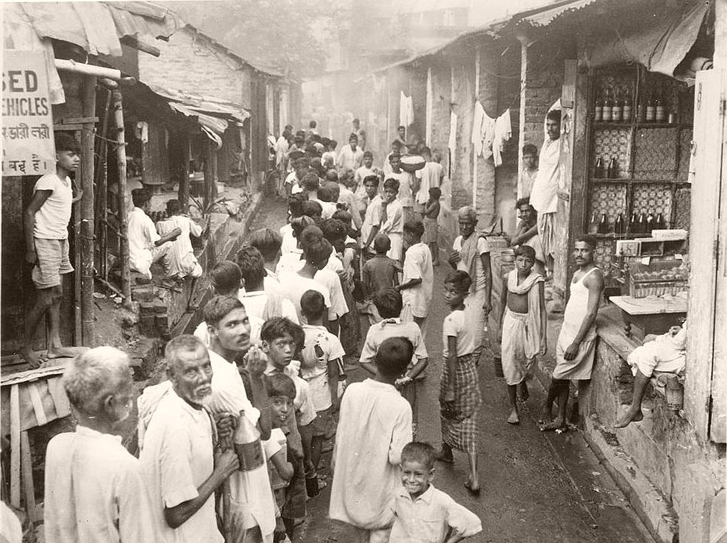 Calcutta's poor from a line to buy keresene at 6 a.m. Each little cubicle may contain a shop and living quarters for a family ranging possibly from 6 to 12. Sanitary facilities consist of an open street drain.