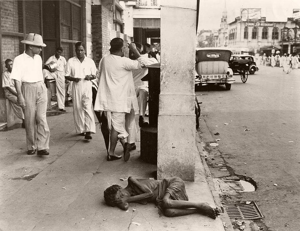 The indifference of the passerby on this downtown Calcutta street to the plight of the dying woman in the foreground is considered common. During the famine of 1943, cases like this were to be seen in most every block, and though less frequent now, the hardened public reaction seems to have endured.