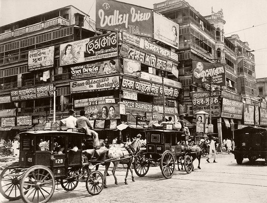 A bewildering mass of billboards at the corner of Harrison Street (Burra Bazar) and Strand Road. One of the oldest sections of Calcutta, at the foot of Howrah Bridge, it is a fine vantage point for photographing the passing parade of oddly dressed natives and curious vehicles.