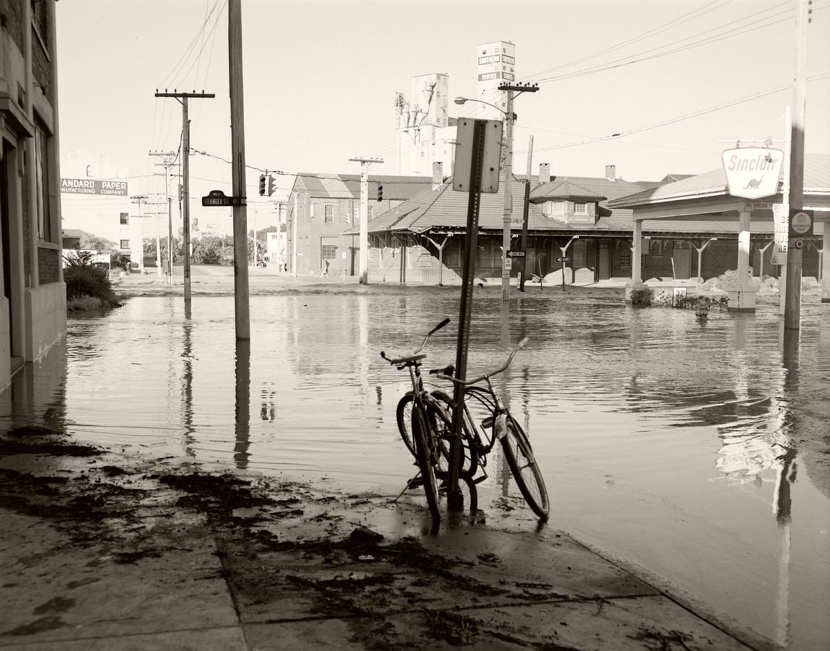 Two bicycles are abandoned at the flooded intersection of Hull Street and 2nd Street, on the southern end of the 14th Street Bridge in Richmond. No. 69-2025, Virginia Governor's Negative Collection, Library of Virginia.