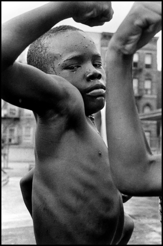 "Leonard Freed A young boy plays ""tough"" in the streets of Harlem. New York City. NY, USA. 1963. © Leonard Freed 