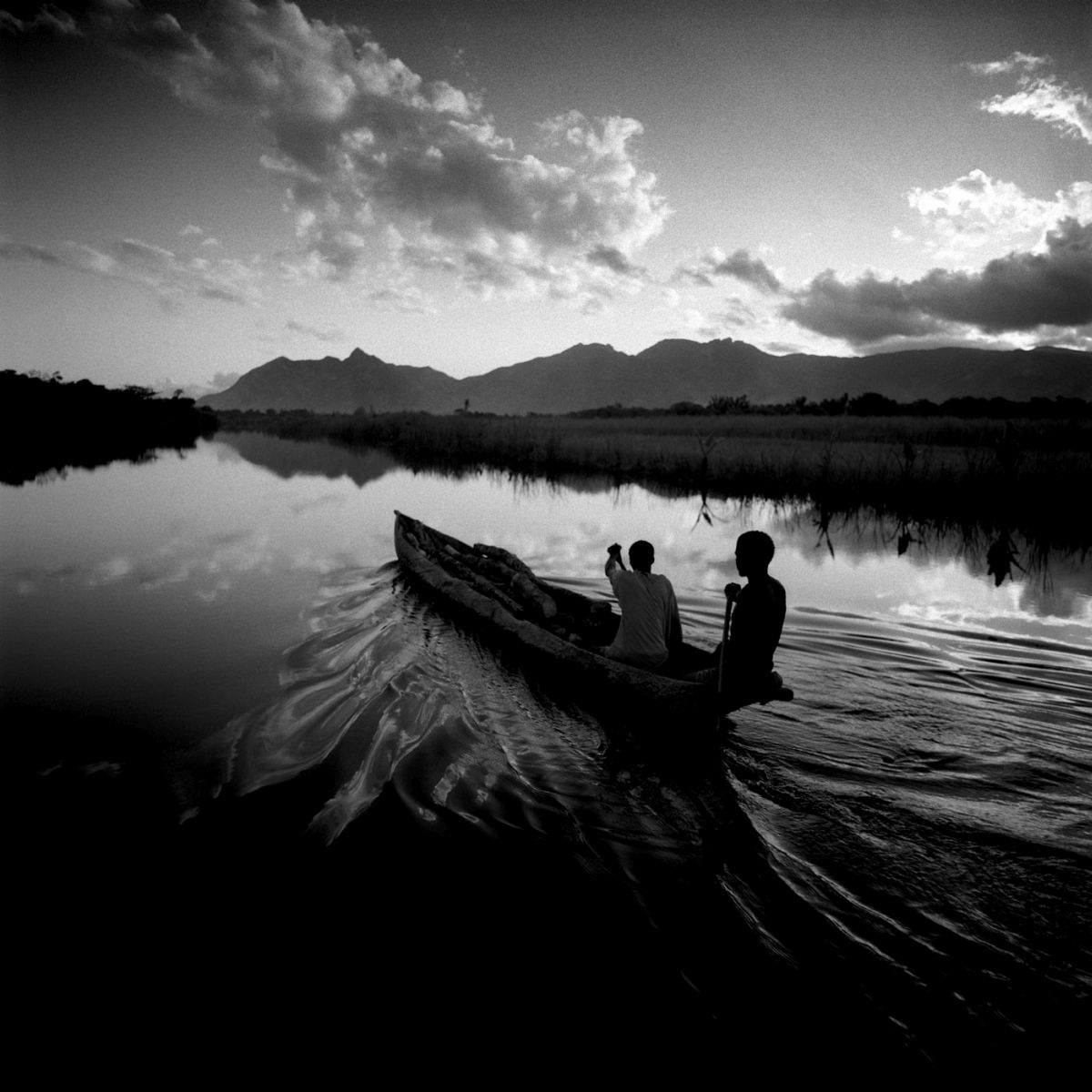 CARNETS DE VOYAGE. CHRIS SIMPSON. Two Men in a Canoe, Madagascar, 1997. Archival pigment print.