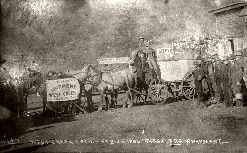 Men standing on and near wagons with a team of four horses, West Creek, Colorado, Feb. 25, 1896