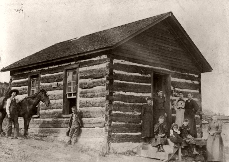 Children and women pose outside the Jarre Creek School, in use from 1888-1908 at the mouth of Jarre Canyon near Highway 67 west of Sedalia, 1898