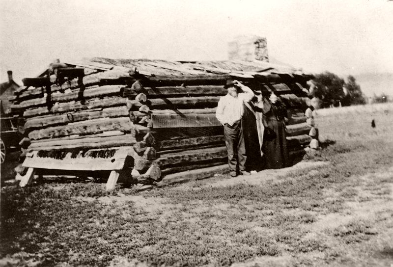 A couple (George Nickson and Sarah Paddison Nickson) stands outside their cabin was which made of logs and has a stone chimneyin the West Plum Creek area, 1887