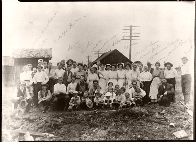 Group of people posed near debris after 'a big fire' in Sedalia, Colorado, 1889