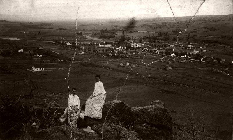 Two young women sitting on Castle Rock, view to the south. Town of Castle Rock is visible in the distance, 1889