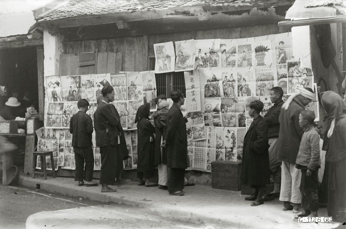 On a Hanoi street, Tet paintings are on sale in 1929. Then, too, Chinese characters, parallel sentences, pictures of flowers, carps, dragons and other, more modern subjects were sold as wall hangings to invite luck into a house for the Lunar New Year.