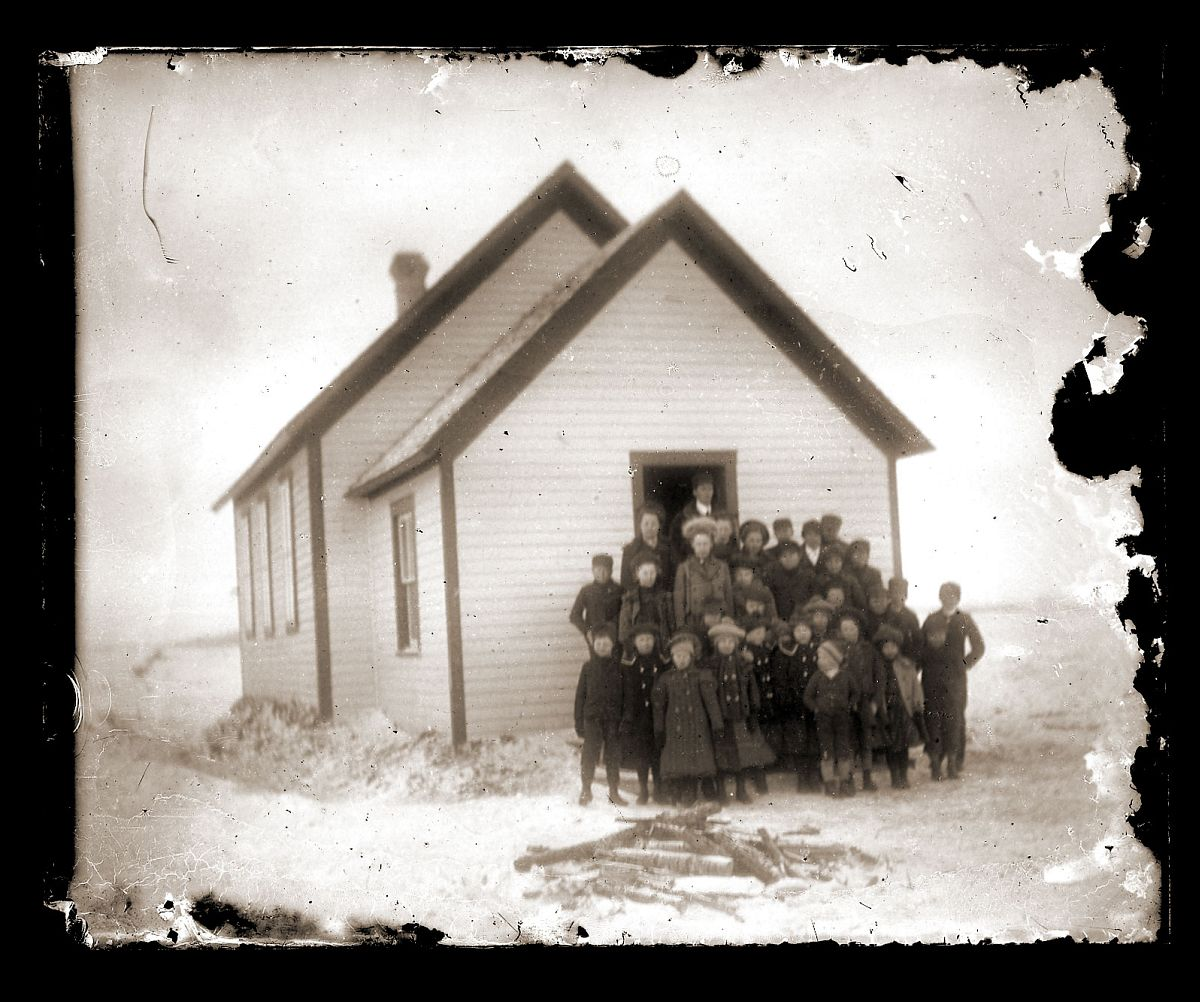 Group of students and teacher posing in front of schoolhouse