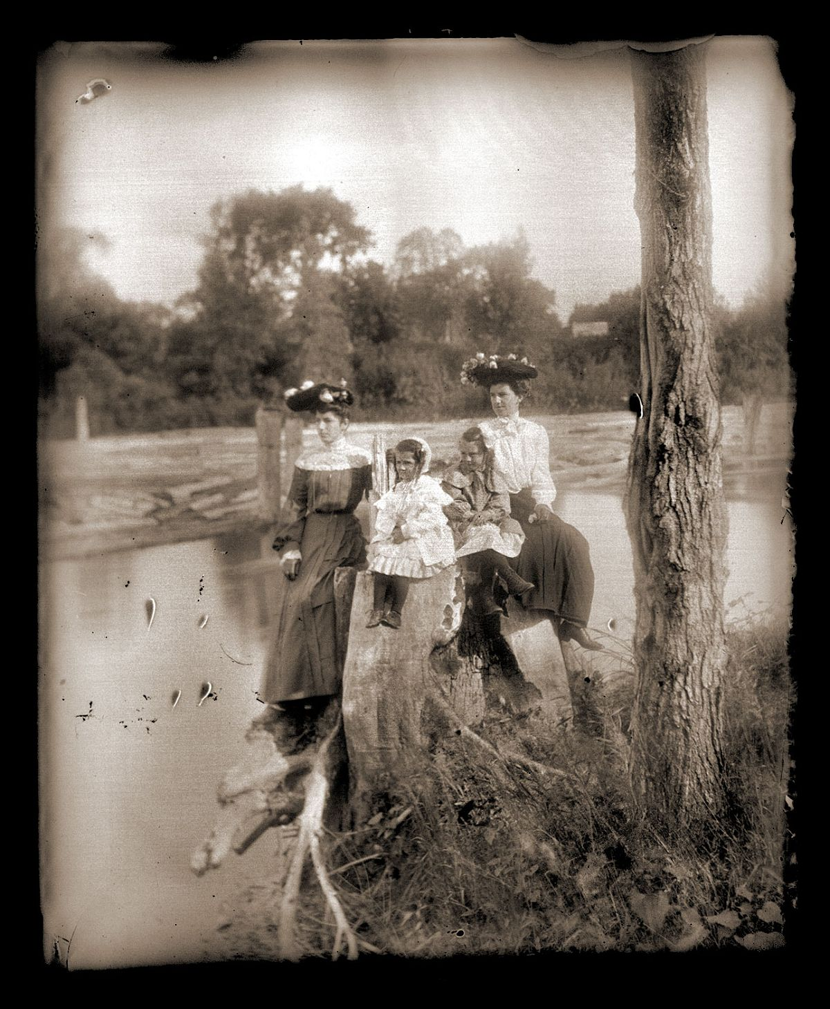 Women and girls posing on a stump by a river