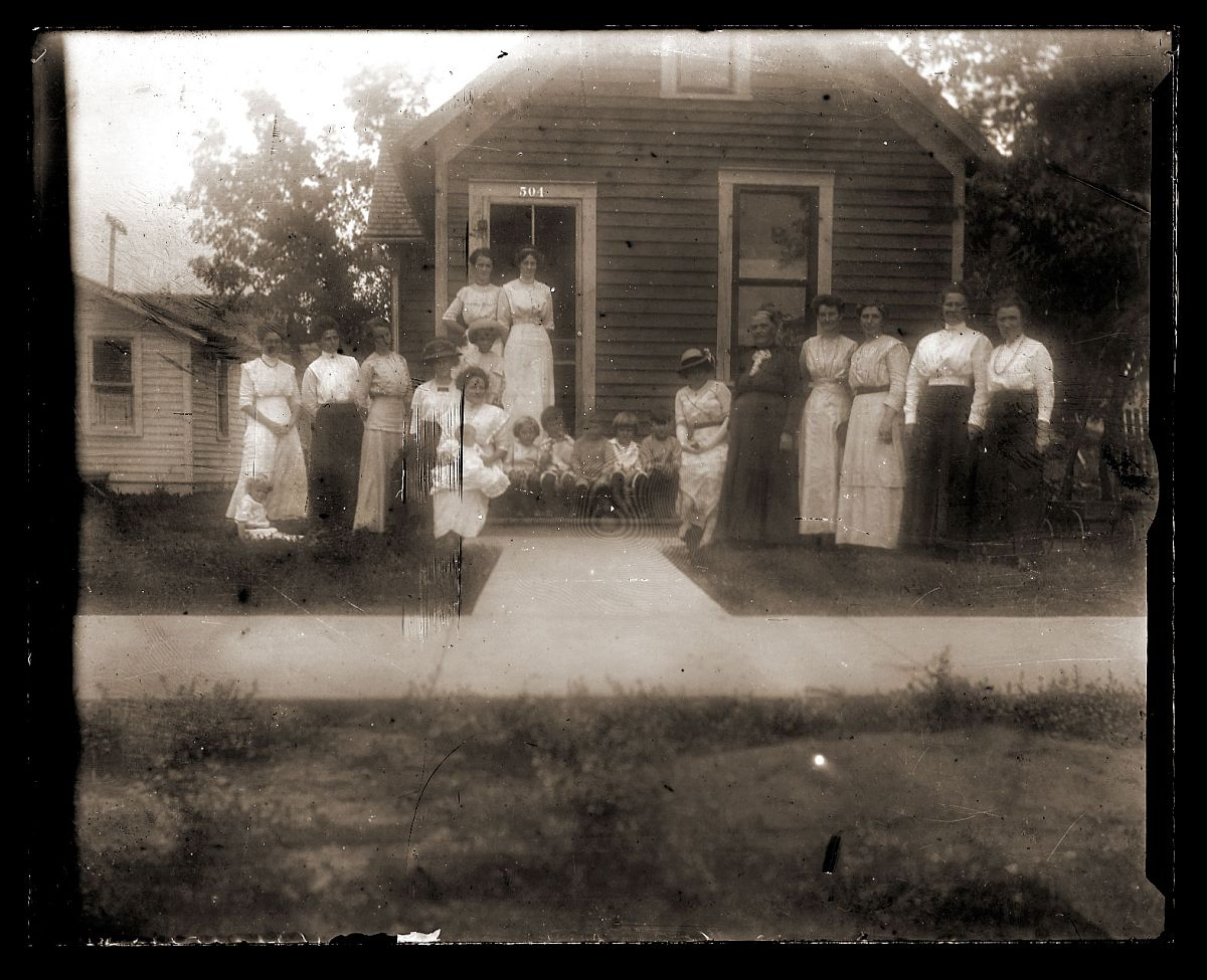 An unidentified group of women and children in front of a house or school