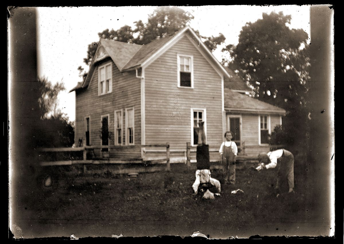 Boys playing in front of a house, c1913