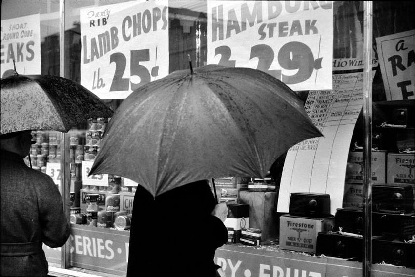 Connecticut. A Woman window shopping on a rainy day in Norwich, November 1940